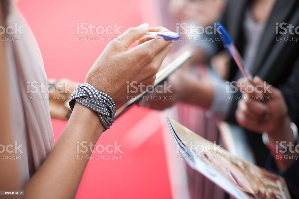 Celebrity signing autographs for fan royalty-free stock photo