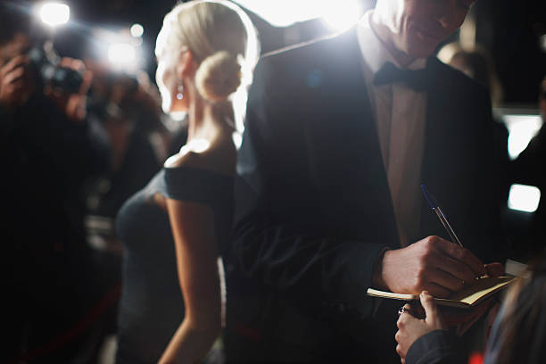 celebrity signing autographs on red carpet - fame stock photos and pictures