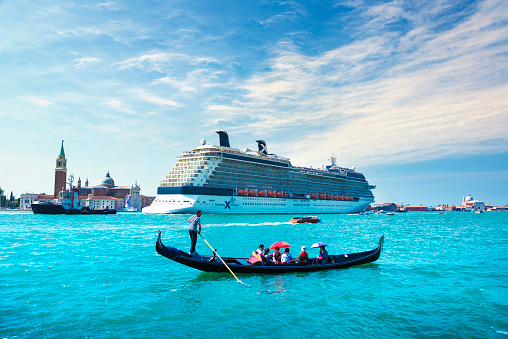 Venice / Italy - July 18, 2013: Celebrity Silhouette cruise ship and tourists in Gondola in Grand Canal.