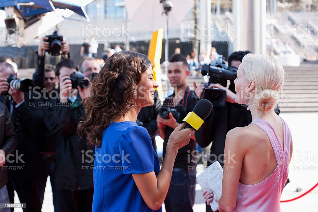 Celebrity speaking to reporters on red carpet royalty-free stock photo