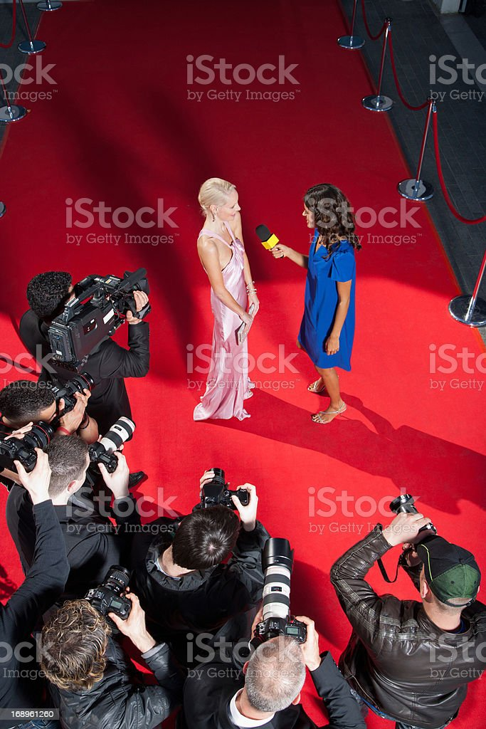 Celebrity talking to reporter on red carpet stock photo