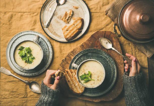sellerie creme suppe in tassen und weibliche hände in pullover - wärmeplatte stock-fotos und bilder