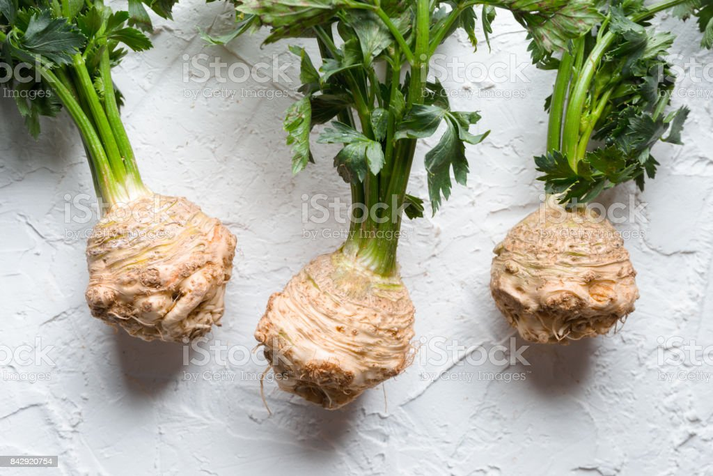 Celery roots with green leaves on a white table stock photo