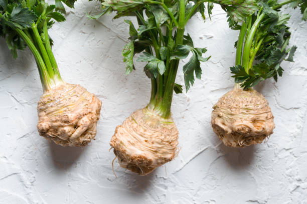 Sellerie-Wurzeln mit grünen Blättern auf einem weißen Tisch – Foto