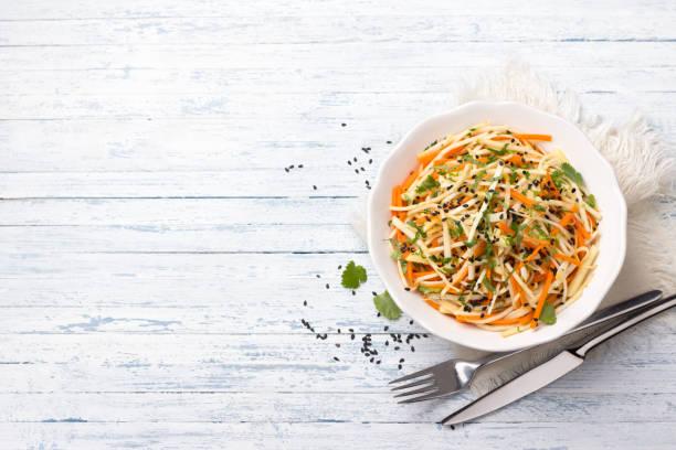 Sellerie Salat mit Karotten, Äpfeln, Cilantro, Sesam und Gewürzen auf blauem Hintergrund – Foto