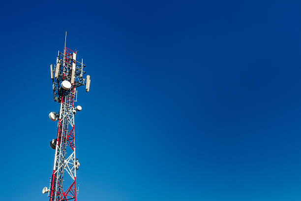 Cell phone antenna tower with blue sky background - foto de stock