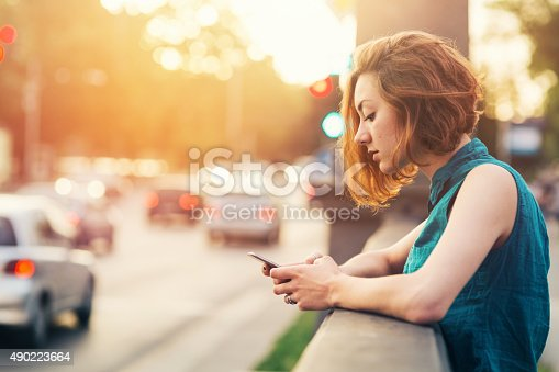 Teenage girl breaking up with her boyfriend while sitting on a bridge near big boulevard. Casual clothing with shirt and jeans.