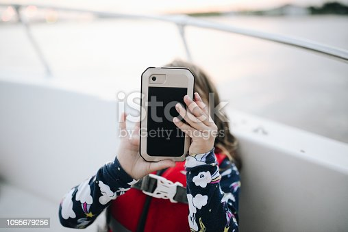 Little girl wearing a life jacket on a boat holds up a cell phone, it is in a protective case. She may be taking a picture or a selfie, it's a good thing the phone has a case. She is a cute 5 year old little girl