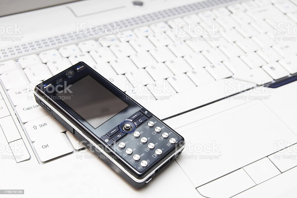 Cell phone on a laptop stock photo