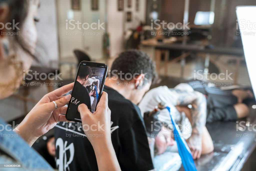 Cell phone photo of a young man tattooed tattooing a man's head стоковое фото