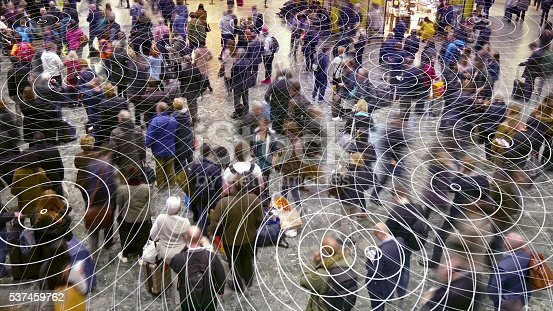 Mobile devices sending out radio waves which spread out in a crowd of people.