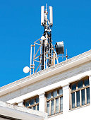 istock Cell phone telecommunications antennas and repeaters on building against clear blue sky 1134871493