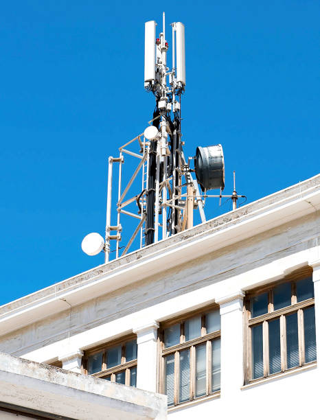 Cell phone telecommunications antennas and repeaters on building against clear blue sky stock photo