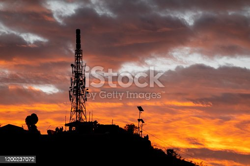 A cell phone tower or communications tower in the early morning sunrise.