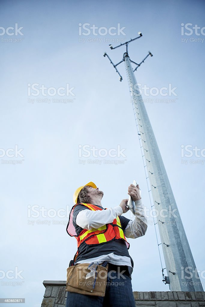 Cell Phone Tower Technician with Tablet Computer stock photo
