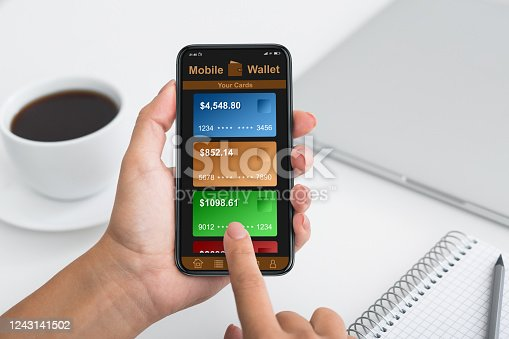 Contactless payments. Cell phone with mobile wallet online shopping on the screen, office table background