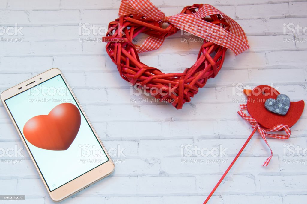 Cell phone with red hearts and a bird on a white background stock photo