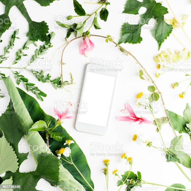 Photo of Cell phone with summer flowers on white background. Wedding, summer, romance concept. Text space