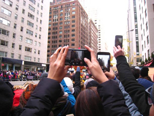 geçit töreninde cep telefonları - geçit töreni stok fotoğraflar ve resimler