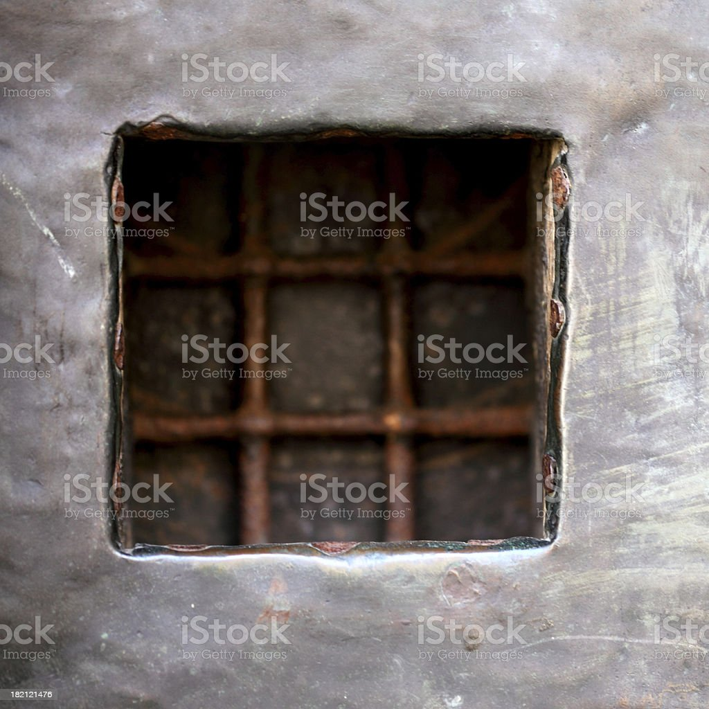 cell window with stell lattice in gray metal wall royalty-free stock photo