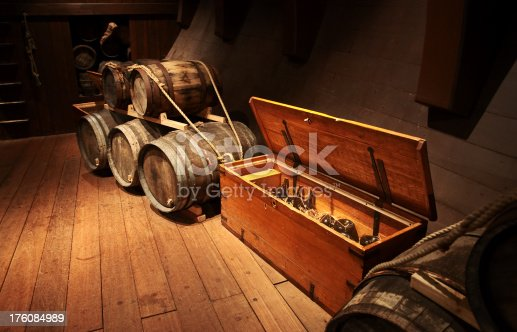 Cellar in moody lights with wooden barrels and old glass bottles in a box.
