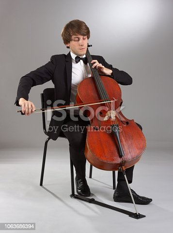 Portrait of the cellist on a light background.