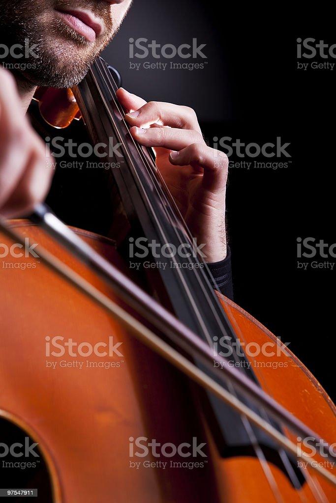 Violoncelliste jouant dans le studio photo libre de droits
