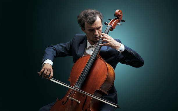 Cellist playing on instrument with empathy stock photo
