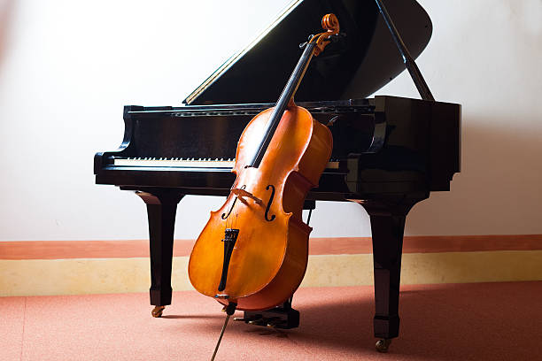 Cello and a piano representing classical music Classical music concept: violin leaning on a piano string instrument stock pictures, royalty-free photos & images