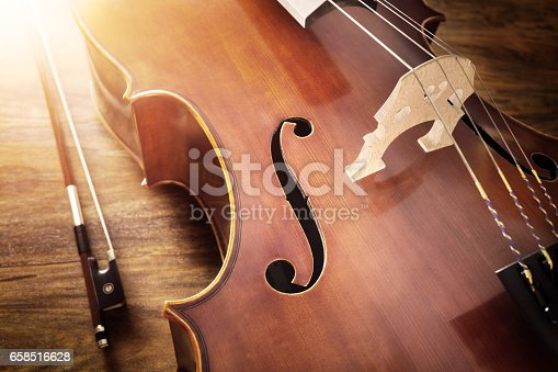 istock Cello on wood background 658516628