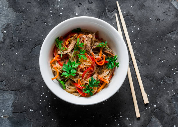 Cellophane noodles with beef, sweet pepper, carrot, onion stir fry on a dark background, top view Cellophane noodles with beef, sweet pepper, carrot, onion stir fry on a dark background, top view rice noodles stock pictures, royalty-free photos & images