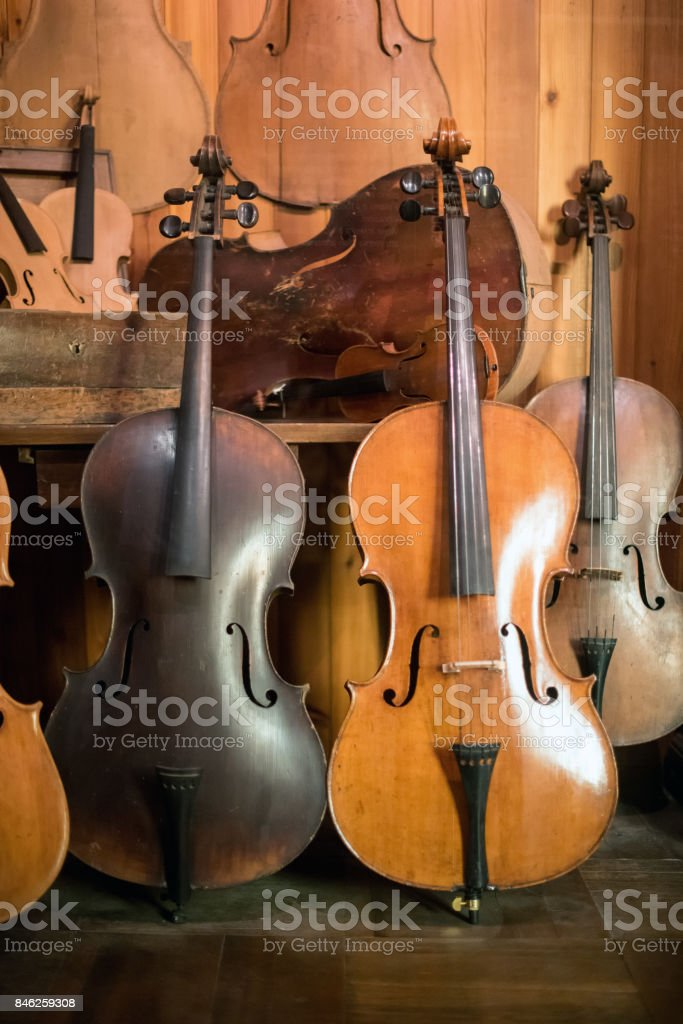 Cellos standing in luthier workshop stock photo