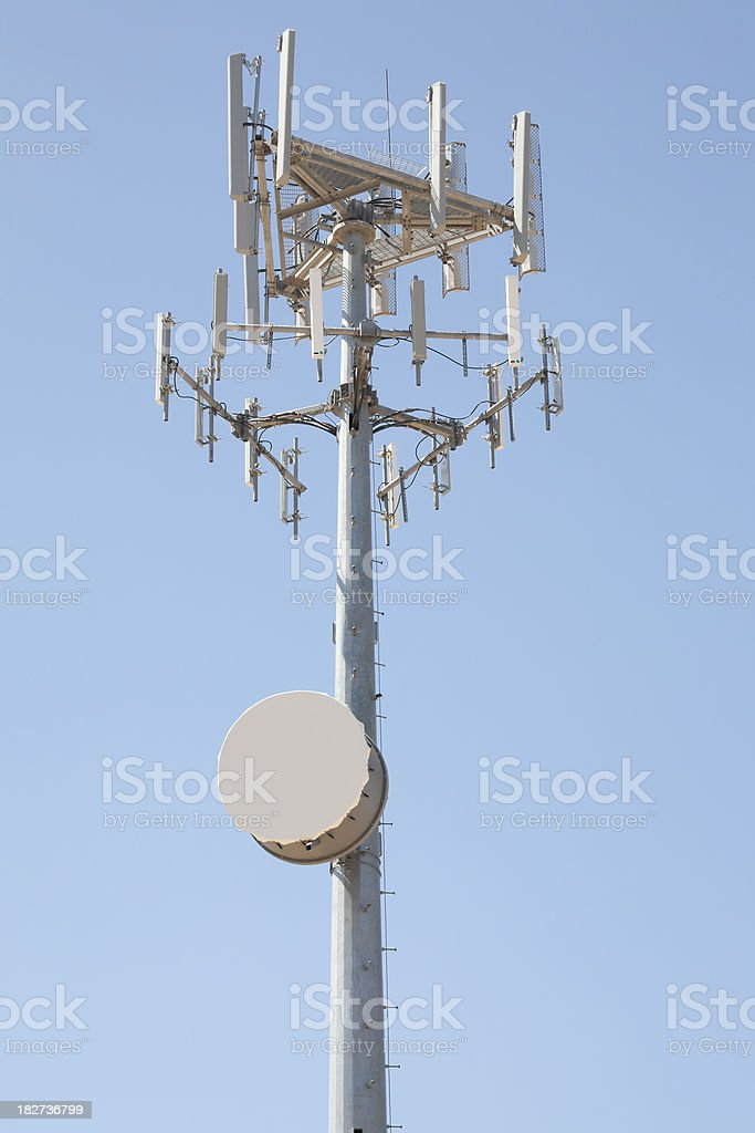 Cellphone and Microwave Tower against Sky stock photo