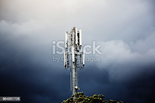Mobile phone transceiver mast stands against a moody sky.
