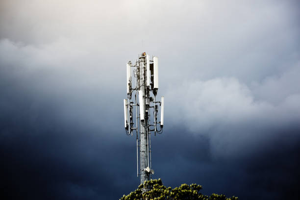 cellphone base station mast against stormy sky - ripetitore per telefoni cellulari foto e immagini stock