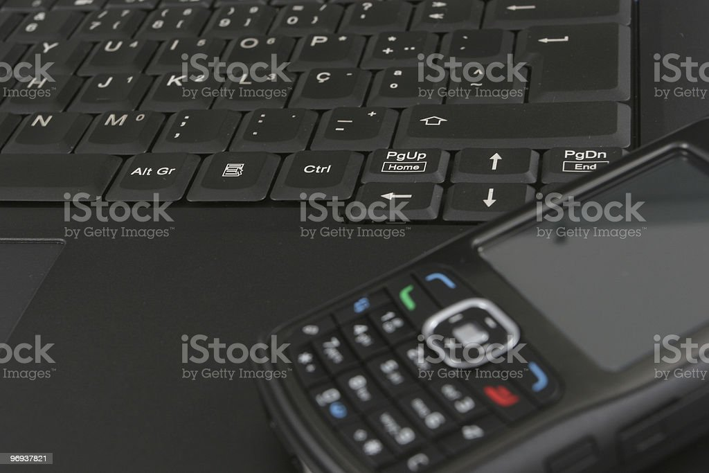 Cellphone isolated over laptop keyboard royalty-free stock photo