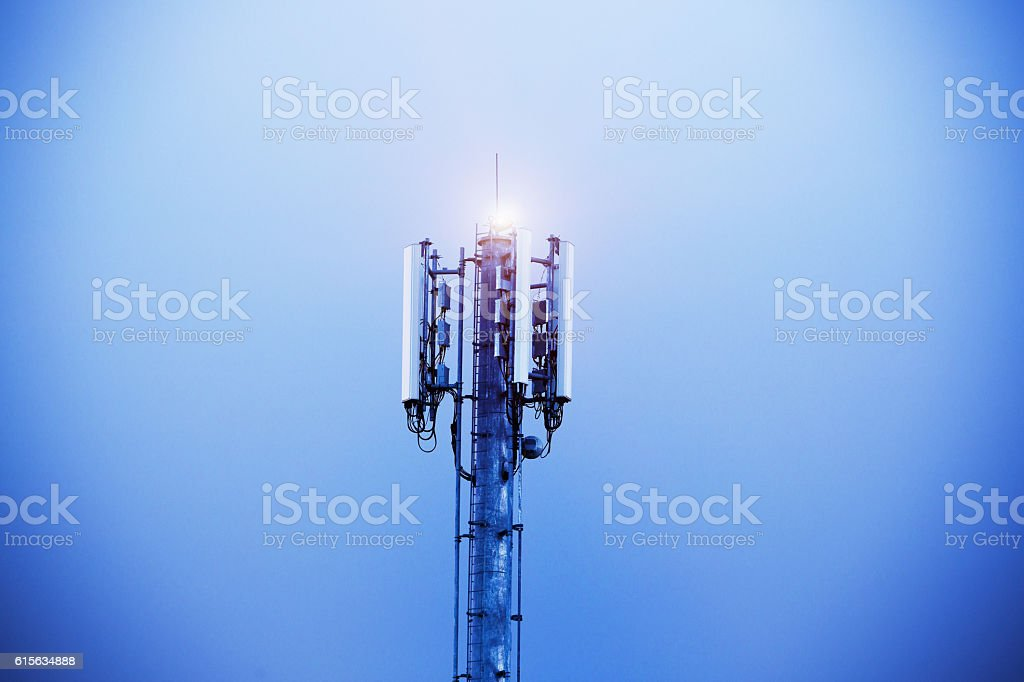 Cellphone tower shining into the evening sky - Foto stock royalty-free di Acciaio