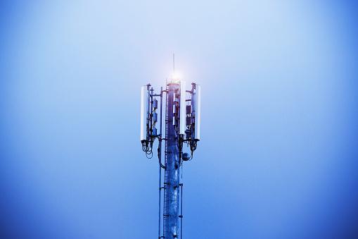 Cellphone Tower Shining Into The Evening Sky - Fotografie stock e altre immagini di Acciaio
