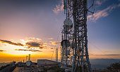 Cellular communications tower for mobile phone and video data transmission at sunset