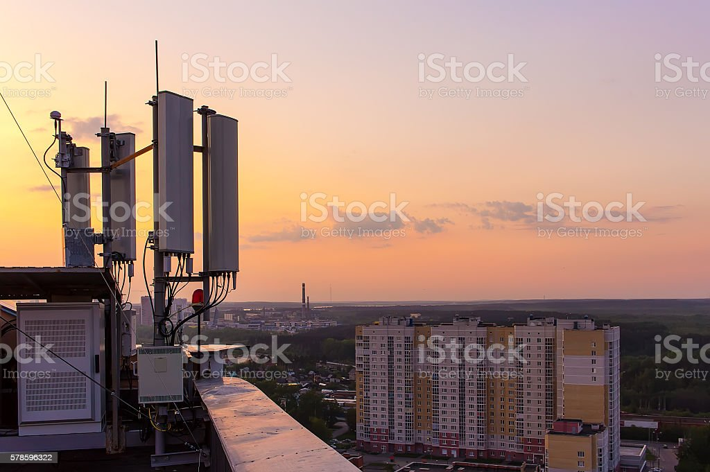 cellular communications tower on background city and beautiful sunset stock photo
