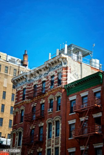 A group of cellular telephone antennas and electronic communications equipment seen on the rooftop of a late 19th century apartment building in Manhattan, New York City.