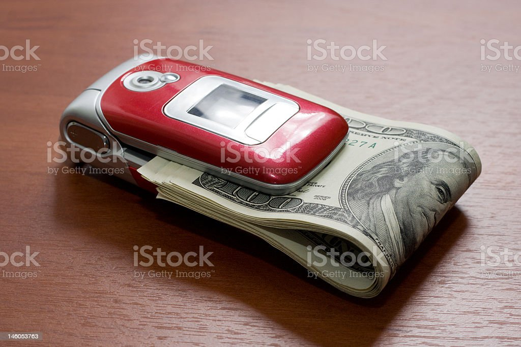 Cellular telephone with a pack of dollars stock photo
