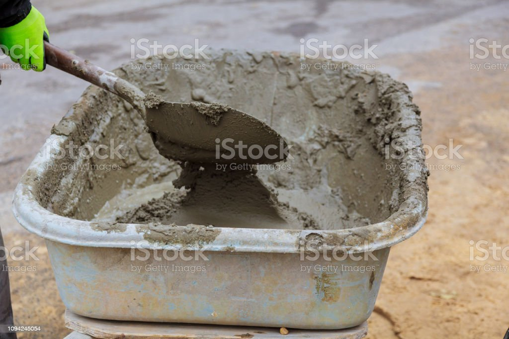 Cemento que se mezcla en una bandeja en el sitio de construcción - foto de stock