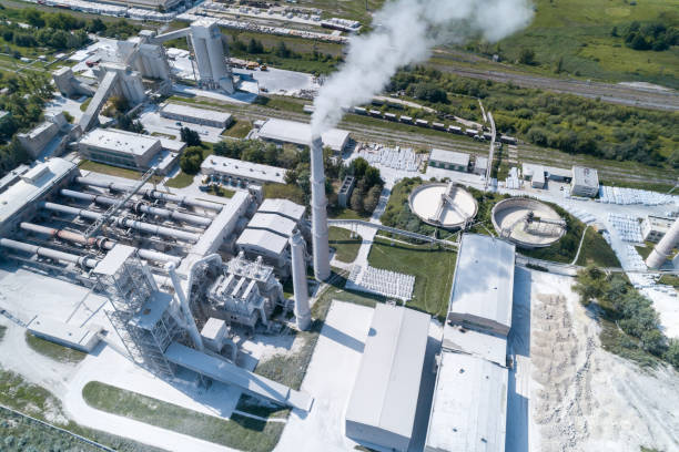 Cement factory, industrial enterprise. The smoking factory chimney stock photo