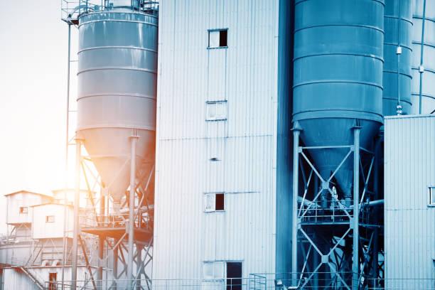 zement-werksmaschine an einem klaren, blauen tag - betonwerkstein stock-fotos und bilder