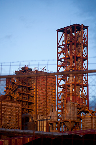 Lugo, Spain-February 18, 2016: Old rusty cement factory at dusk, seen from the road outside, clear sky background.