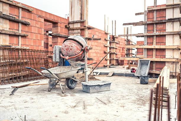betonmischmaschine maschine auf baustelle, tools schubkarre, sand - betonwerkstein stock-fotos und bilder