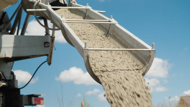 Cement on the troughs follows from the concrete mixer. Delivery of ready-made high-quality concrete concept The concrete is unloaded from the concrete mixer. Against the blue sky. Construction of country houses. concrete stock pictures, royalty-free photos & images