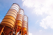 Cement silos of Cement batching plant factory against evening warm clear sky with space for text