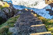 istock Cement stairs down to Ensenada de La Mina, Prellezo, Spain 1212355466